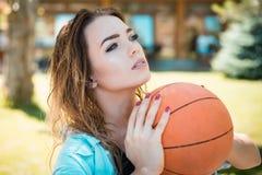 Combinación estimulante de habilidad y de fuerza técnicas Jugador de básquet sensual que tira una bola Mujer bonita con fotos de archivo libres de regalías