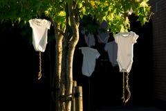 Combinaison blanche accrochante de bébé dans l'arbre, sur le fond foncé photo stock