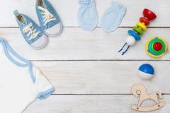 Combinaison de bébé et jouets de bébé sur le fond en bois Configuration plate Images libres de droits