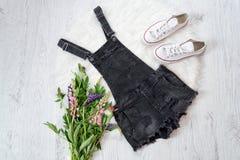 Combinaisons grises de denim, un bouquet des fleurs, espadrilles concept à la mode Images stock