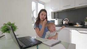 Combinando el trabajo y el parenting, madre con el griterío poco hijo mientras que trabaja en el ordenador portátil y habla en el metrajes