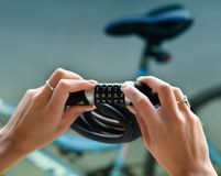 Combination bike lock in female hands. Close up of female hands holding combination bike lock with bicycle blurred in background Stock Photos