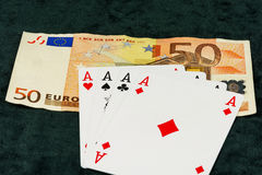 The combination of four aces lying on banknotes Royalty Free Stock Photo