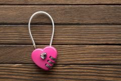 Combination lock heart shape on wooden background. Combination lock in heart shape on wooden background Stock Photography