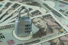 Combination lock pad on pile of japanese yen banknotes as financ. Ial safe haven or security concept Royalty Free Stock Images