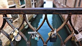 A combination of locks on a bridge in Venice, Italy. Sunny day, canal in the background stock photography