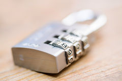 Combination padlock close up with chrome numbers on wooden backg. Round Royalty Free Stock Photography