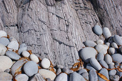 The combination of round and striped stones. The combination of round and striped rocks on the sea shore Stock Photo