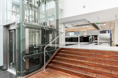 Combination of technology and nature at the entrance. Glass lift and wooden stairs leading to the lobby Royalty Free Stock Photos
