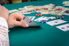 Combination of two aces in female hands on poker table stock photos