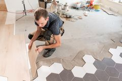 Male worker installing new wooden laminate flooring. The combination of wood panels of laminate and ceramic tiles in the royalty free stock photography