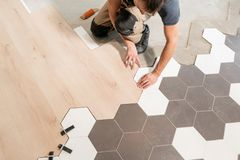 Male worker installing new wooden laminate flooring. The combination of wood panels of laminate and ceramic tiles in the royalty free stock images