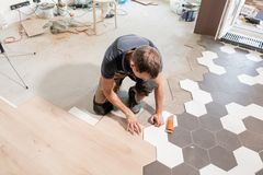 Male worker installing new wooden laminate flooring. The combination of wood panels of laminate and ceramic tiles in the stock photography