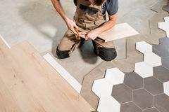 Male worker installing new wooden laminate flooring. The combination of wood panels of laminate and ceramic tiles in the stock photo