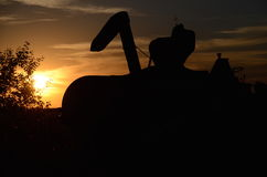 Combine auger silhouetted. The auger and hopper of an old combine is silhouetted in the sunset Royalty Free Stock Photo
