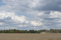 Combine on a field with cloudy skies Stock Images