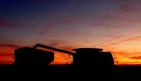 Combine and Grain Cart at Sunset. Silhouette of combine dumping grain into grain cart at sunset Stock Photos