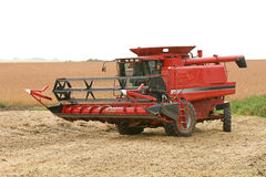 Combine Harvester. A large red combine harvester with soy bean head Royalty Free Stock Image
