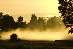 Combine Harvester. A combine harvester in a field at sunset Stock Photography