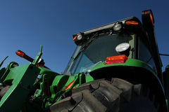 Combine Harvester. Green combine harvester as viewed from ground level against clear blue sky royalty free stock photos