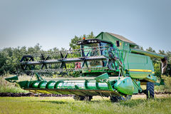 Combine harvester in action on wheat field. Varna, Bulgaria - July 10th 2015. Modern John Deere combines harvesting grain in the field near the town Varna Royalty Free Stock Photography