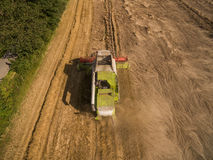 Combine harvester - Aerial view of modern combine harvester at the harvesting the wheat on the golden wheat field in the summer Royalty Free Stock Image