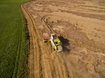 Combine harvester - Aerial view of modern combine harvester at the harvesting the wheat on the golden wheat field in the summer Stock Photo