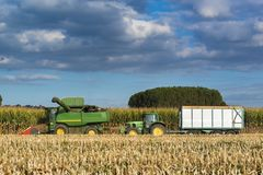 Combine harvester corns followed by a tractor with the trailer Stock Photography