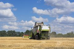 Combine-harvester in the field to gather the harvest of grain crops. Rye, wheat royalty free stock photography