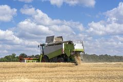 Combine-harvester in the field to gather the harvest of grain crops. Rye, wheat royalty free stock image