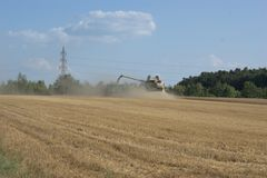 Combine harvester harvesting grain and processing it and pouring it into a trailer pulled by a tractor. A combine harvester harvesting grain and throwing up Stock Photography