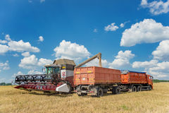 Combine harvester loading grain into a transport truck Stock Photos