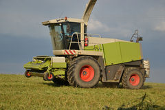 Combine harvester mows the field, harvester unloading into a tractor trailer. Slovakia Stock Photography