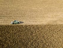 Combine harvester picking seed from fields, aerial view of a field with a combine harvester with cornhusker gathering the crop. Agriculture and cultivation Stock Image