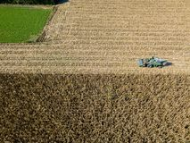 Combine harvester picking seed from fields, aerial view of a field with a combine harvester with cornhusker gathering the crop. Agriculture and cultivation Royalty Free Stock Images