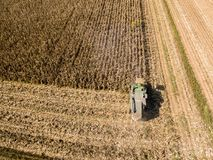 Combine harvester picking seed from fields, aerial view of a field with a combine harvester with cornhusker gathering the crop. Agriculture and cultivation Stock Photo