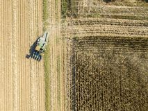 Combine harvester picking seed from fields, aerial view of a field with a combine harvester with cornhusker gathering the crop. Agriculture and cultivation Royalty Free Stock Photography