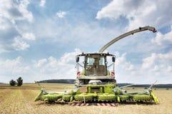 Combine harvester and thresher. Modern agricultural combine harvester and thresher standing in a freshly harvested field Stock Photos