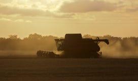 Combine harvester twilight. Combine harvester harvesting crop at twilight Stock Photography