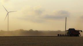 Combine harvester twilight wind generator. Combine harvester harvesting crop and wind generator Stock Photo