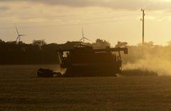 Combine harvester twilight wind generators. Combine harvester harvesting crop and wind generators Stock Image