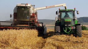 Combine harvester unloading grain into the truck