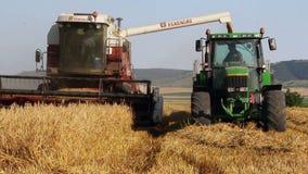 Combine harvester unloading grain into the truck stock footage