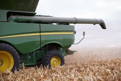 Combine harvester working in a field. Harvesting the fall maize crop in a close up partial side view with the arm Royalty Free Stock Image