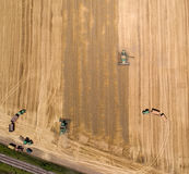Combine harvester working in golden wheat field. Aerial image of combine harvester and tractors working in ripe golden wheat field. Harvesting in summer time Royalty Free Stock Photos