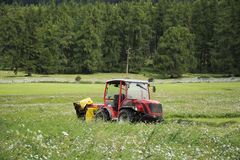 Combine harvesters machinery stop waiting works outdoors. At grass field near Burgusio or Burgeis village at Malles Venosta, in val Venosta, in Trentino-Alto Royalty Free Stock Image