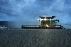 Combine harvesting at twilight Royalty Free Stock Images
