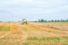 The combine is harvesting a wheat field in autumn. The combine is harvesting a wheat field in autumn Royalty Free Stock Photos