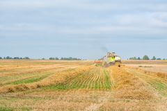 The combine is harvesting a wheat field in autumn. The combine is harvesting a wheat field in autumn Stock Photography