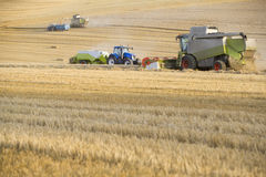 Combine harvesting wheat and straw baler in field Royalty Free Stock Photography